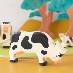 Vaca blanca y negra pastando - Animal de granja de madera